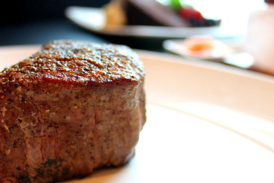 A cut of thick steak from Level 2 Steakhouse on a white plate.