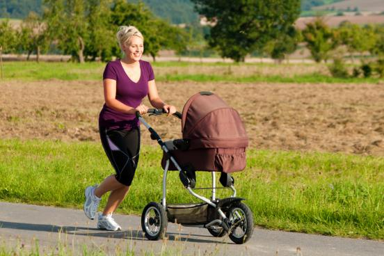 Mom pushing stroller with child inside during an outdoor jog in Branson.