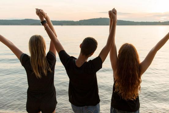 Three girls holding hands and staring into the sunset at Table Rock Lake in Branson.