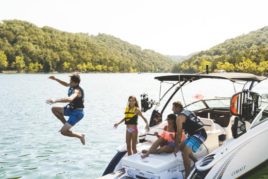 Family of four jumping off back of boat at a scenic lake in Branson.