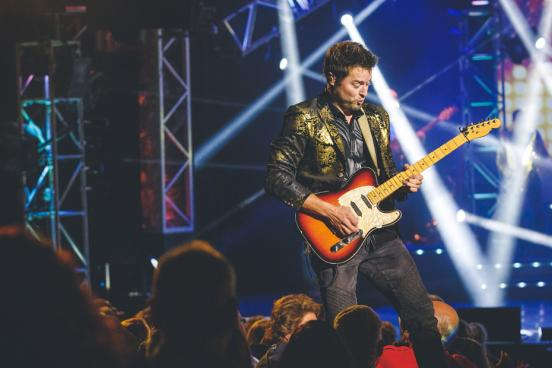Man playing guitar in front of a large crowd at a Branson live show.
