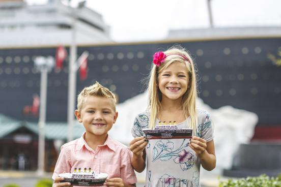 Brother and sister holding toy Titanic ships in front of a large Titanic replica in Branson.