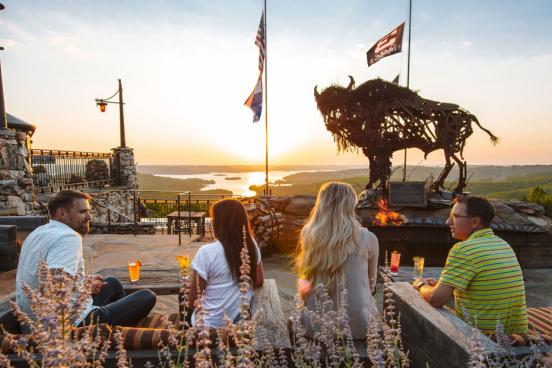 Two couples on a date at an upscale restaurant in Branson that overlooks a lake and a sunset.