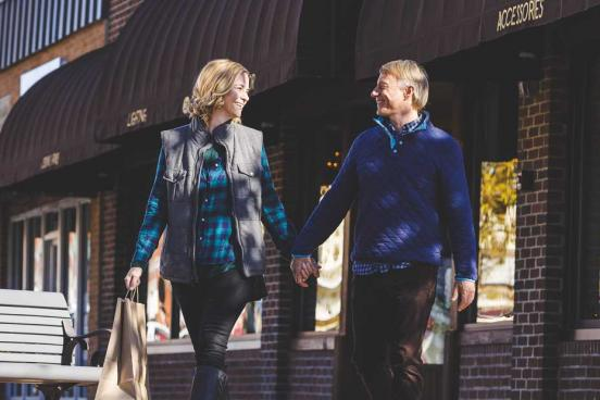 Man and women holding hands and walking through Downtown Branson.