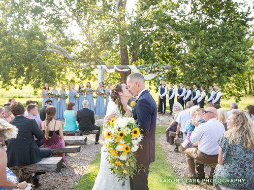 Recently married couple kissing at the end of the aisle at an outdoor wedding venue underneath a large sycamore tree.