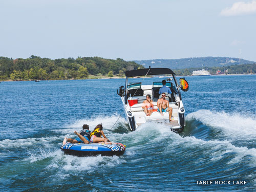 Family of four pulling a tube behind a speedboat in Branson.