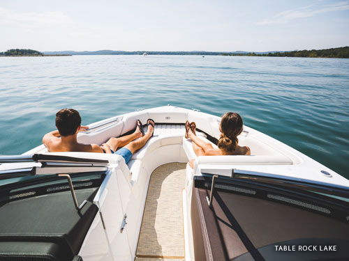 Man and women sitting on the front of a speed boat on a lake in Branson.