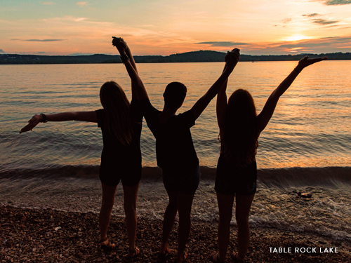 Three girls holding hands and staring into the sunset at Table Rock Lake.