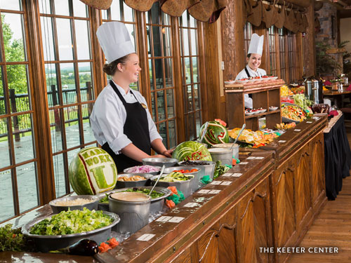 Two college students serving guests food at a buffet-style restaurant in Branson.