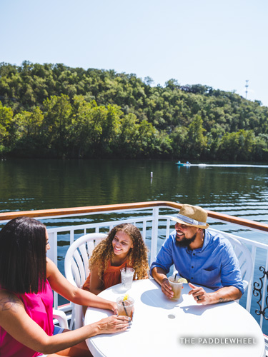 Family of three enjoying an outdoor patio meal on the bank of Lake Taneycomo.