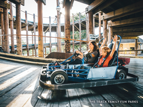 Mom and son riding a go-kart on a three story wooden track in Branson.