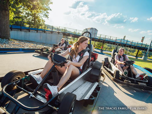 Three girls driving go-karts at a family fun park in Branson.