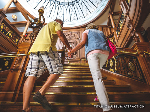 Couple holding hands and walking up a grand staircase at an interactive Titanic attraction in Branson.
