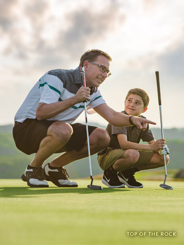 Father and son reading a putt on a golf course in Branson.
