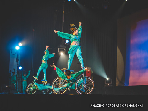 Four Chinese acrobats riding trick bikes on stage during a Branson live show.