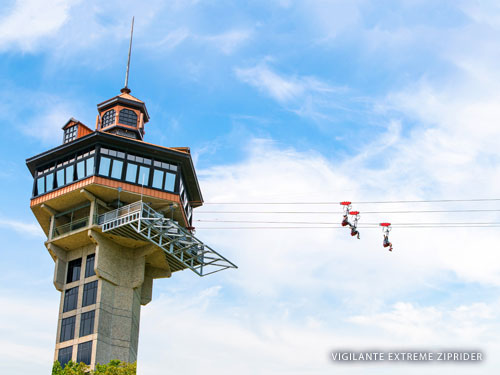 Three zipline riders sliding down a zipline from a tall tower in the Ozark Mountains.