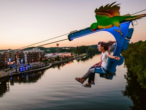 A man and women flying over a lake in Branson on a zipline towards an outdoor shopping center.